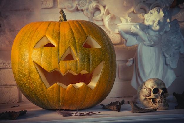 Calabaza y cráneo de halloween están sobre la mesa