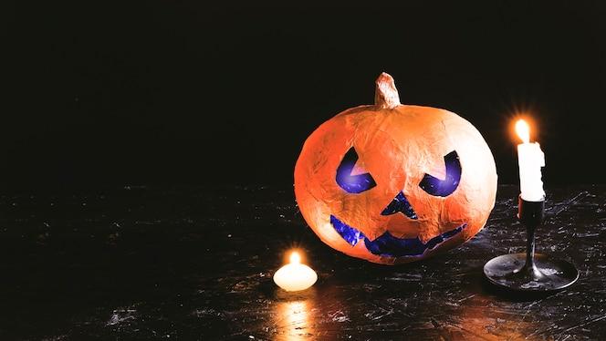 Calabaza decorativa de halloween con cara tallada iluminada en el interior con velas encendidas