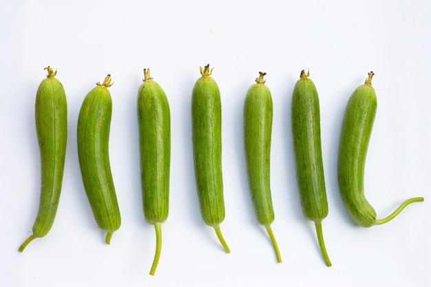 Calabaza de esponja verde fresca o luff sobre superficie blanca