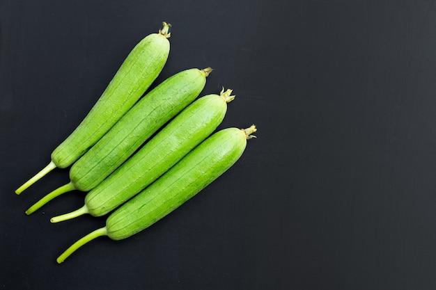 Calabaza de esponja verde fresca o luff sobre superficie oscura