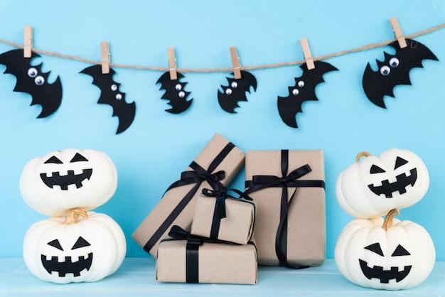 Calabaza fantasma blanco con caja de regalo y bate sobre fondo azul cielo