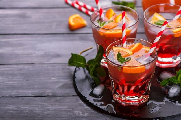 Calabaza fresca con naranjas, refrescos, jarabe de frambuesa, hojas de menta en una mesa de madera oscura