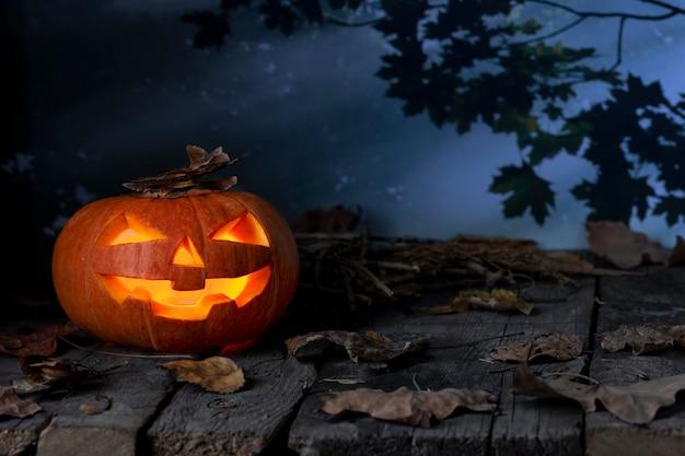 Calabaza de halloween brillando en un bosque místico en la noche. jack o lantern horror. diseño de halloween con copyspace.