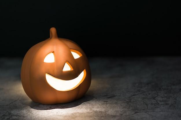Calabaza de halloween de cerámica sonriente iluminada por dentro y desde arriba con una luz cálida sobre una superficie desgastada con textura gris oscuro con fondo negro y espacio para editar