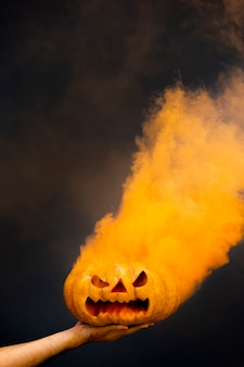 Calabaza de halloween espeluznante con humo naranja