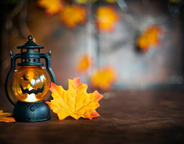 Calabaza de halloween en hojas de otoño y jack o lantern en textura de fondo de madera marrón halloween