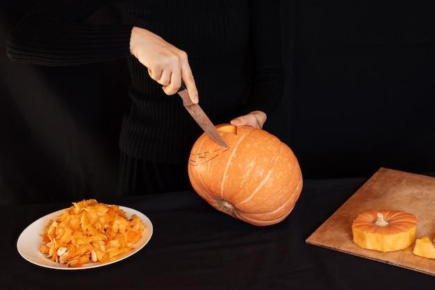 La calabaza de halloween de jack. la mano de la niña con un cuchillo cortando una calabaza naranja