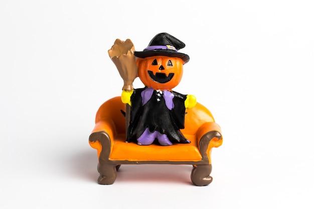 Calabaza de halloween del mago que se coloca en un sofá anaranjado.