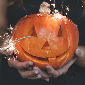 Calabaza de halloween en manos de una niña con luces de bengala. concepto de vacaciones de halloween. bella mujer con calabazas.
