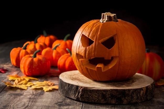 Calabaza de halloween en mesa de madera y fondo negro