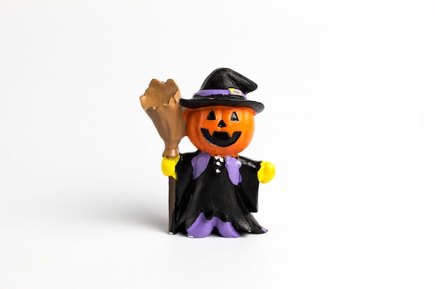 Calabaza de halloween de muñeca de mago con una escoba.