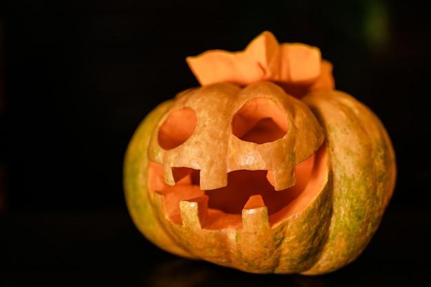 Calabaza de halloween naranja con cara divertida en el fondo oscuro. jack-o-lantern en la celebración de halloween
