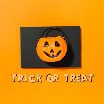 Calabaza de halloween en pedazo de papel negro con inscripción trick or treat