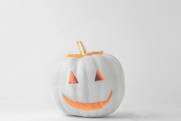 Calabaza de halloween pintada de blanco sobre una superficie blanca
