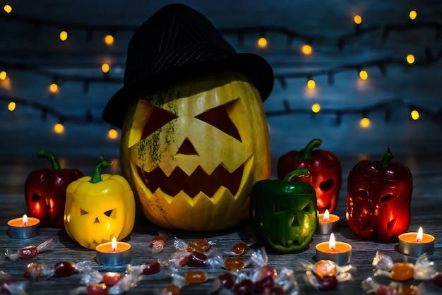 Calabaza de halloween con sombrero con cara terrible rodeada de pimientos con caras aterradoras. guirnalda ligera, caramelos, llama, noche.