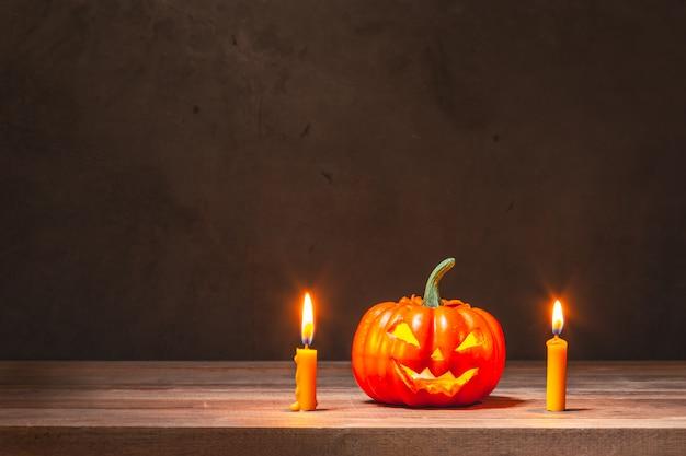 Calabaza de halloween y velas amarillas en mesa de madera