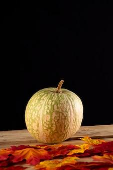 Calabaza con hojas de otoño sobre tabla de madera