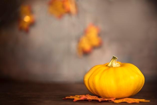Calabaza madura y hojas de otoño sobre la mesa de madera sobre fondo marrón con copia espacio decorativo c