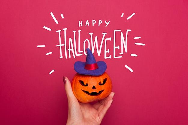 Calabaza en una mano femenina en un sombrero de bruja azul con letras de feliz halloween