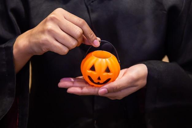 Calabaza en mano, niña vestida con traje negro en la fiesta de halloween