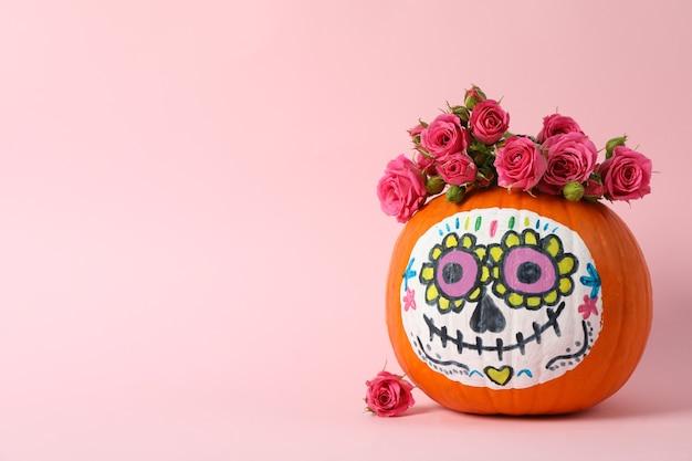 Calabaza con maquillaje de calavera de catrina y flores sobre fondo rosa