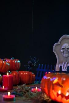 Calabaza naranja con cara de miedo y velas se encuentra sobre una mesa de madera. celebración de halloween. quema de velas de halloween.