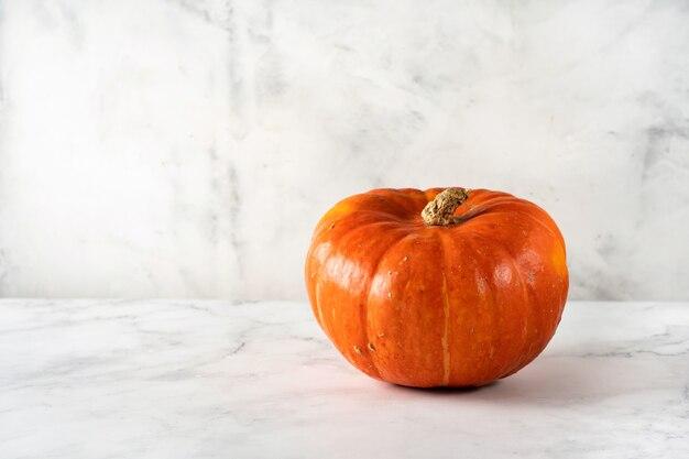 Calabaza naranja sola sobre superficie blanca. copia espacio