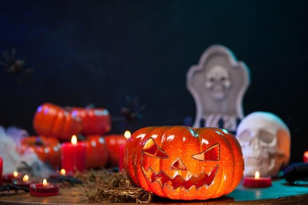 Calabaza naranja tallada con una cara espeluznante para la celebración de halloween. cráneo de miedo en la mesa de madera.