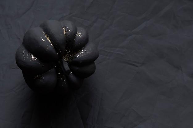 Calabaza pintada de negro con brillo dorado sobre un fondo negro arrugado para tu proyecto de halloween
