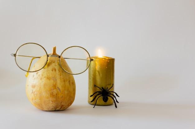 Calabaza seca disfrazada con vasos y velas y araña decoración mínima para halloween espacio de copia