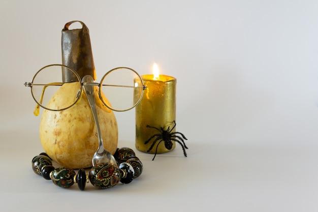 Calabaza seca disfrazada con vasos y velas y decoración de araña para halloween espacio de copia