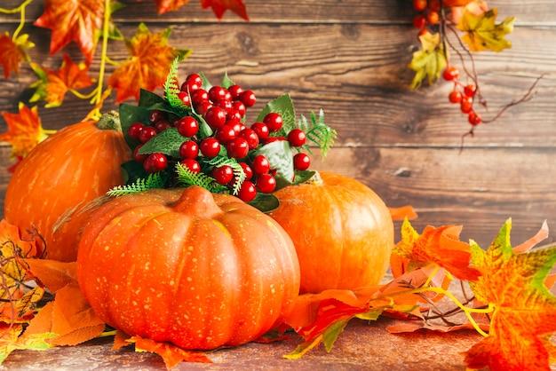 Calabazas y bayas entre hojas de otoño