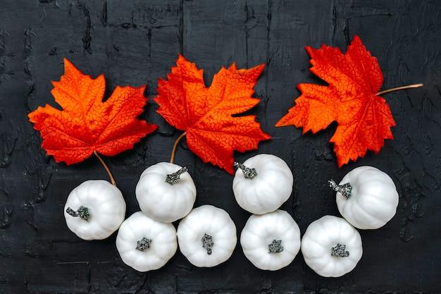 Calabazas blancas con hojas de arce en negro con textura publicidad festiva pancarta plana. celebración de decoración de halloween. color de composición de moda, copyspace