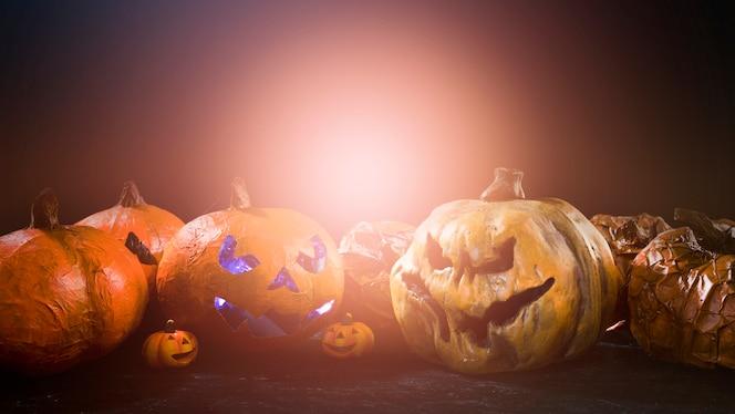 Calabazas caseras de halloween con caras enojadas talladas y luz detrás