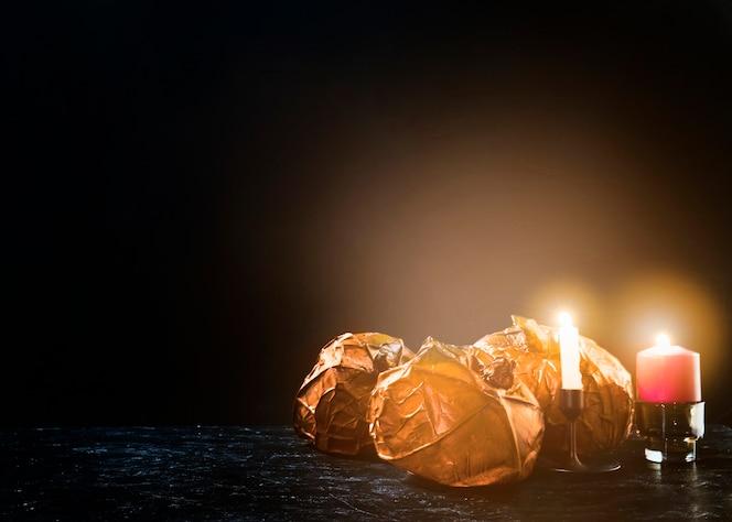 Calabazas decorativas de color naranja acostado de lado cerca de velas encendidas