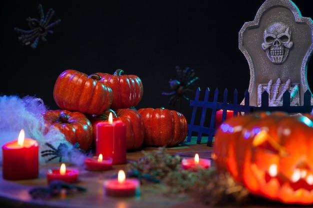 Calabazas embrujadas en halloween con velas encendidas en una mesa de madera. piedra mortuoria espeluznante.