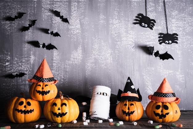 Calabazas fantasmas naranjas con sombrero de bruja sobre tabla de madera gris