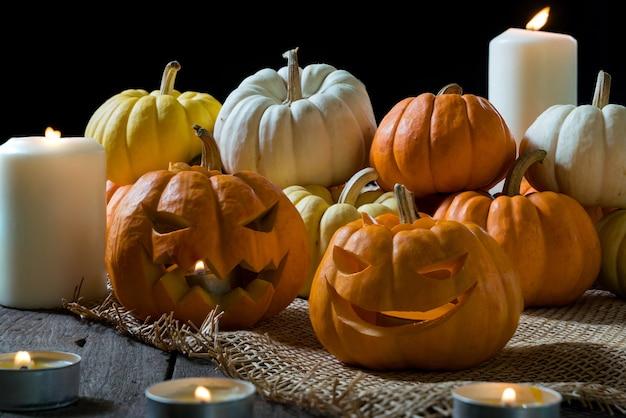 Calabazas de halloween con cara de jack o lantern y decoración de luces de velas.