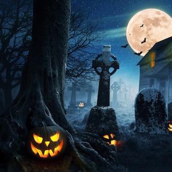 Calabazas de halloween cerca de un árbol en un cementerio con una casa aterradora. fondo de halloween en el bosque de noche con luna y murciélagos.