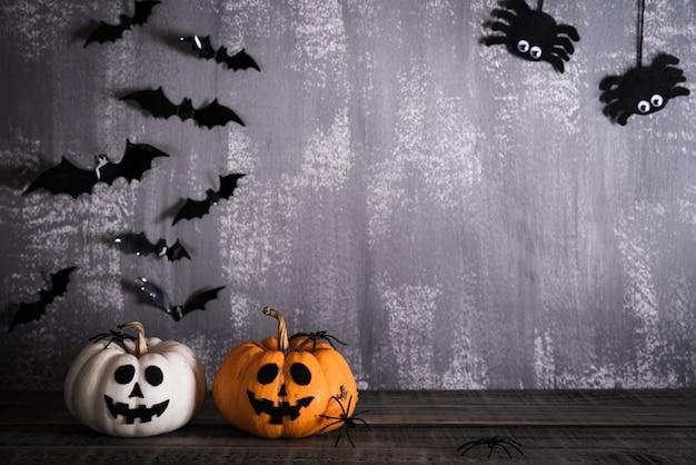 Calabazas de halloween fantasma naranja sobre fondo gris tablero de madera con murciélago.