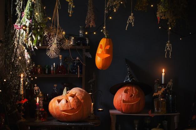 Calabazas de halloween con luces y velas encendidas y pociones mágicas en la casa de la bruja