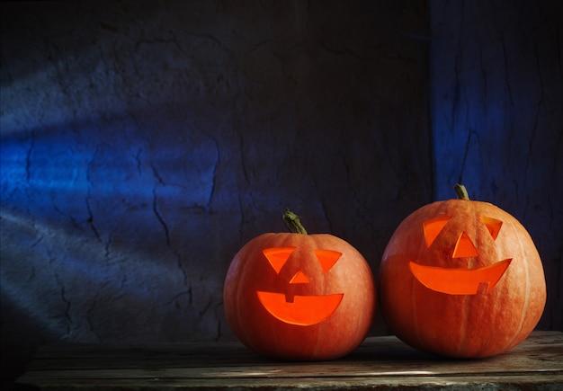 Calabazas de halloween en mesa de madera sobre fondo oscuro