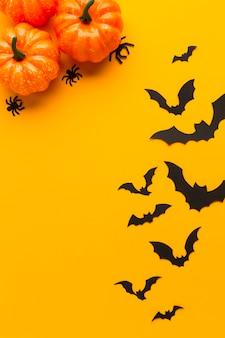 Calabazas de halloween y murciélagos con fondo naranja