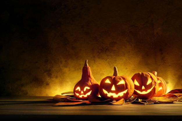 Calabazas de halloween de noche fantasmagórica en madera.