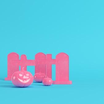 Calabazas de halloween rosa con cruces y lápidas sobre fondo azul brillante
