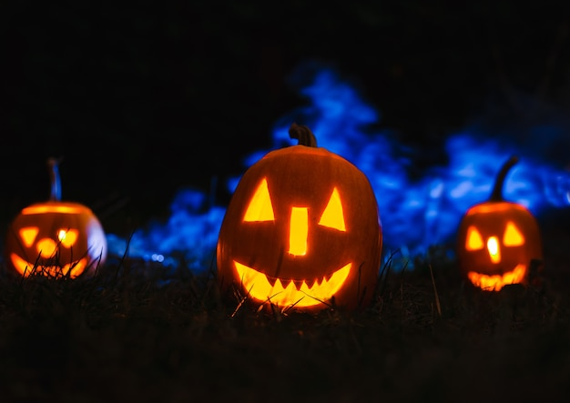 Calabazas de halloween sobre azul con humo