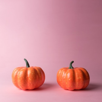 Calabazas de halloween sobre un fondo rosa