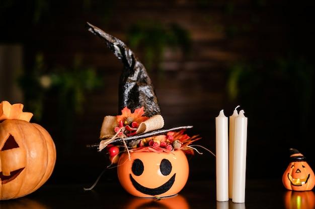 Calabazas de halloween con sombrero de bruja negro sobre su fondo de madera. jack-o-lantern en la celebración de halloween