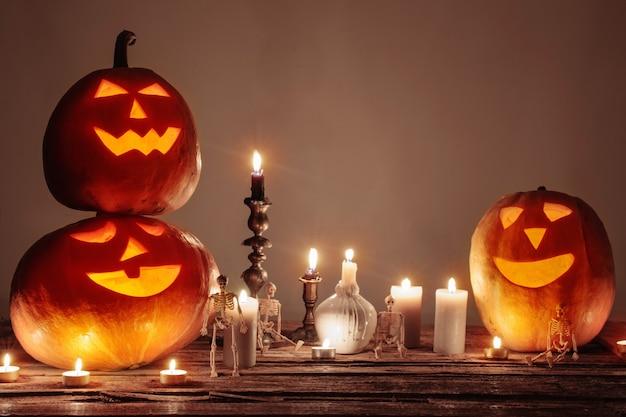 Calabazas de halloween con velas en la mesa de madera