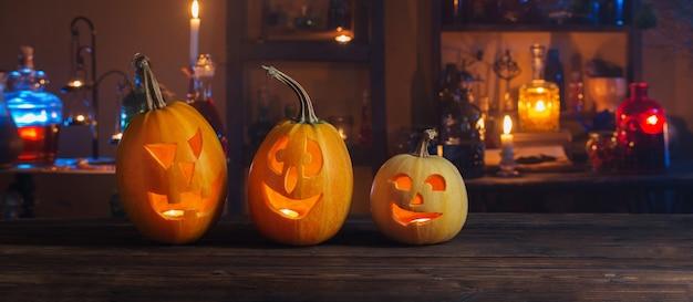 Calabazas de halloween con velas y pociones mágicas en la noche interior